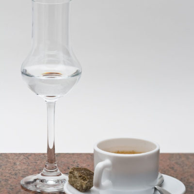 4400081 — Grappa Glass With Espresso In Cup On Granitplate With Espresso Beans